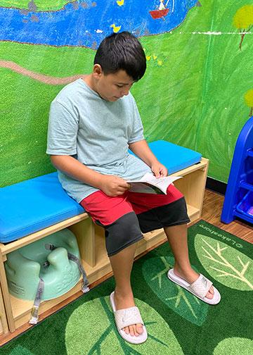 Boy reading on blue bench